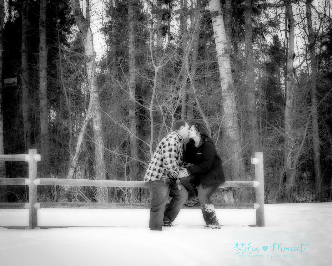 a couple sit on a fence and kiss in the winter snow