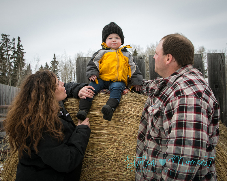 a little boy sits atop a bale while dad and mom look on