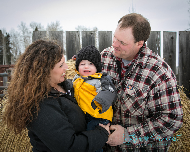 a mom and dad hold their smiling son while standing in front of a bale