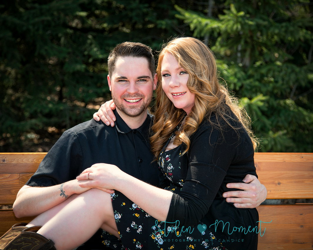 a man sits on a park bench with his fiance on his lap and they both smile for the camera