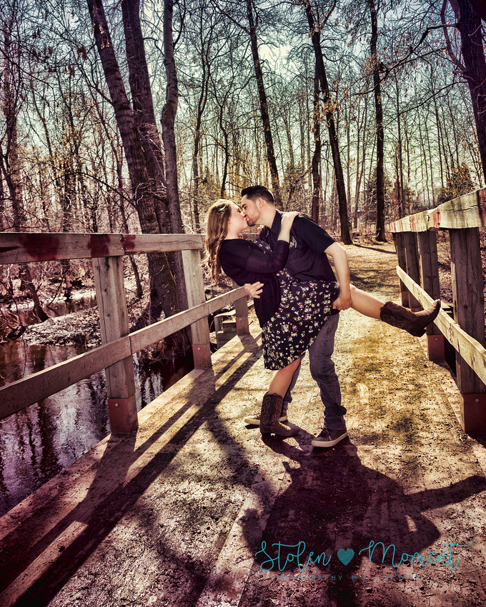 a man dips his fiance on a bridge and leans in for a kiss