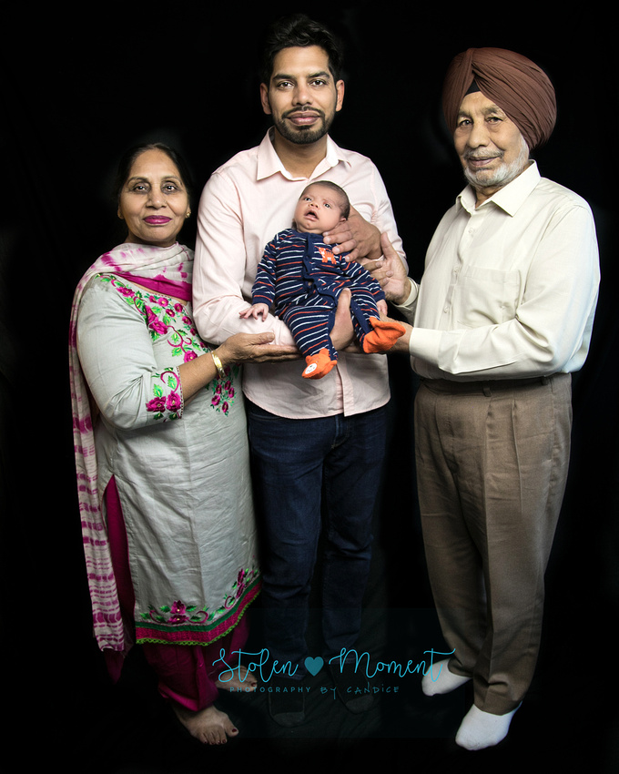 a dad holds his new son while his dad and mom stand on either side of him