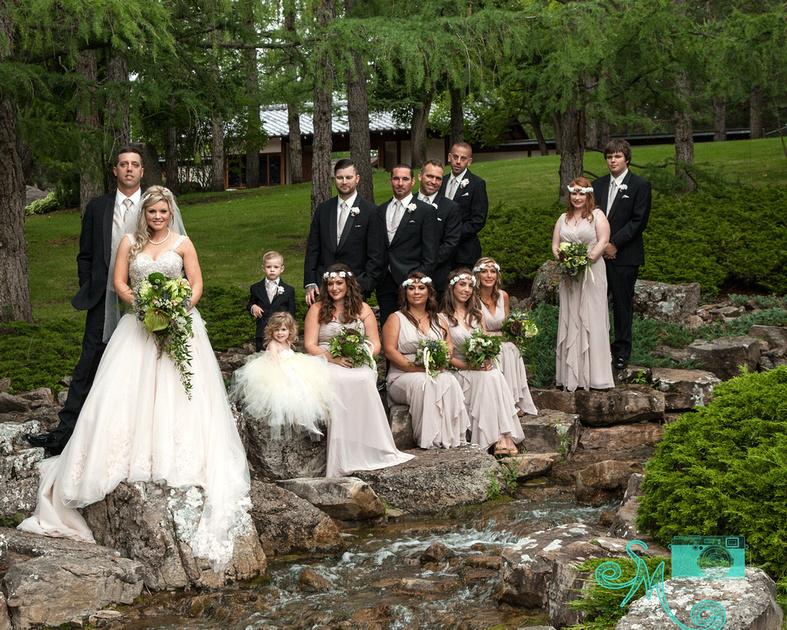 wedding party of fourteen standing on rocks near waterfall