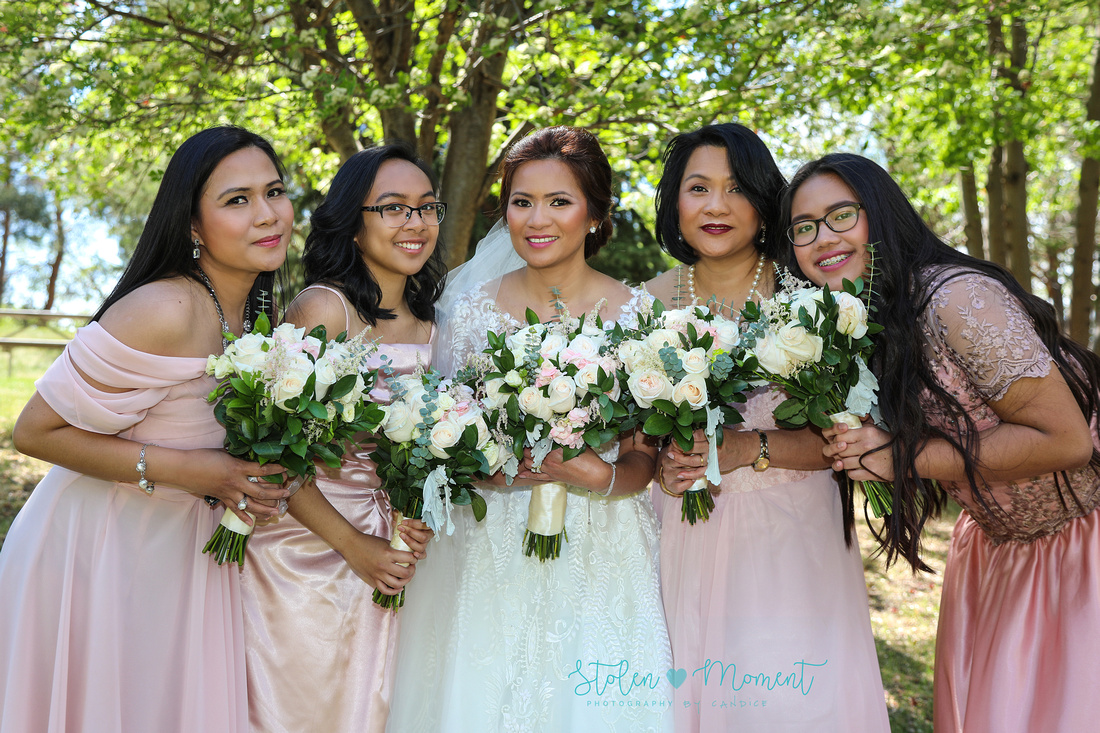 The bride and her bridesmaids hold their bouquets close to each other as they lean in to each other in front of the trees on the grounds  of the Muttart Conservatory