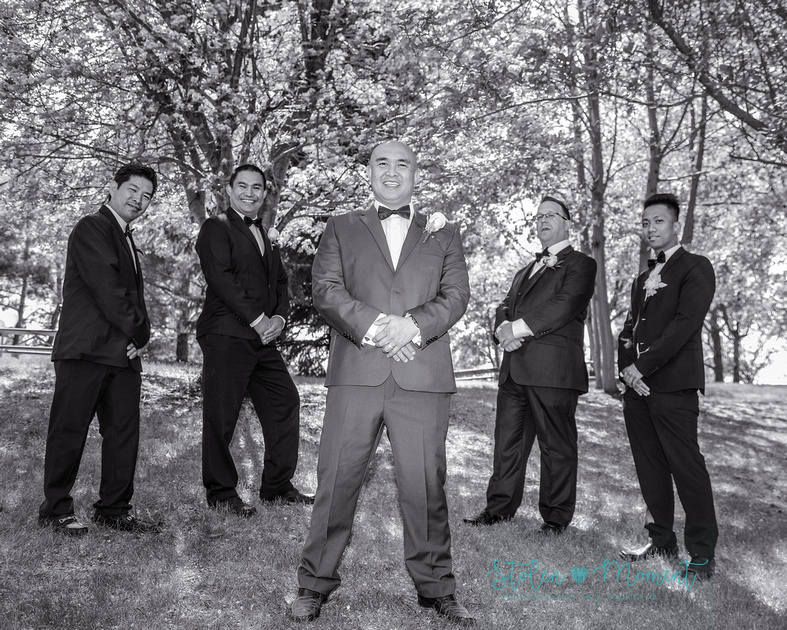 the groom stands in front of his four groomsmen at the trees on the grounds of the Muttart Conservatory