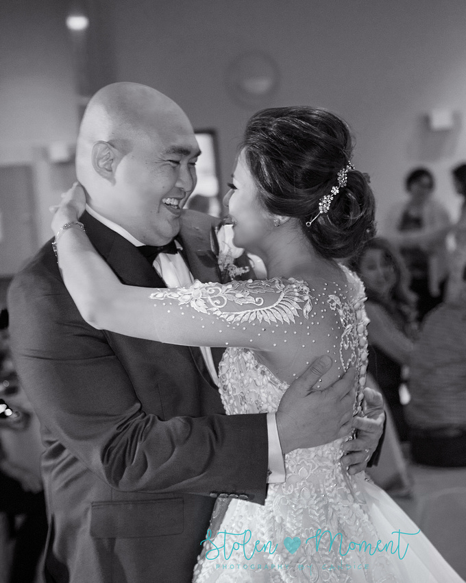 the bride and groom share their first dance and smile looking into each other's eyes