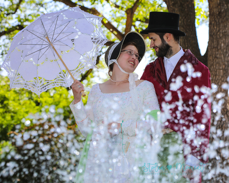 an engaged couple dressed in 18th century costume, look into each other's eyes while photo is taken through water at a water fountain at the Alberta Legislature grounds