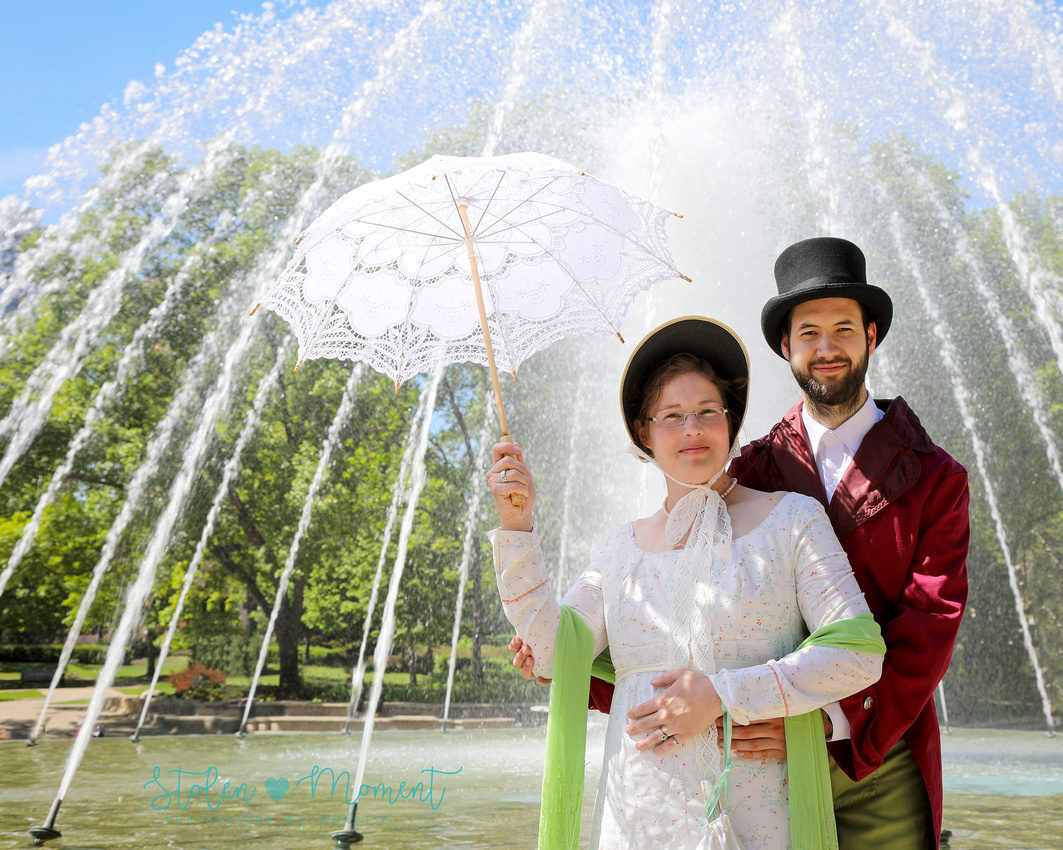 an engaged couple dressed in 18th century costume pose in front of the fountain at the Alberta Legislature Grounds