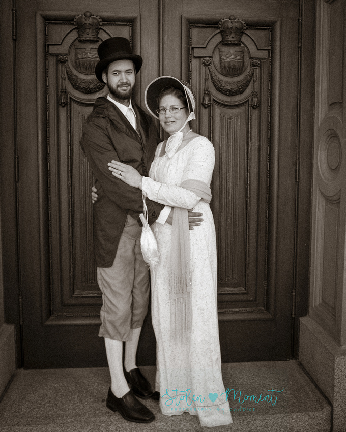 an engaged couple in 18th century costumes pose in front of the doors at the Alberta Legislature