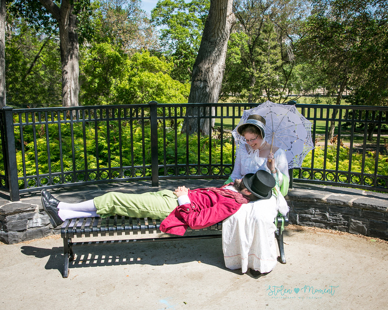 a man dressed in 18th century costume, lays across the bench in Lois Hole garden at the Alberta Legislature grounds resting his head in the lap of his fiance while resting his hat over his face from the sun