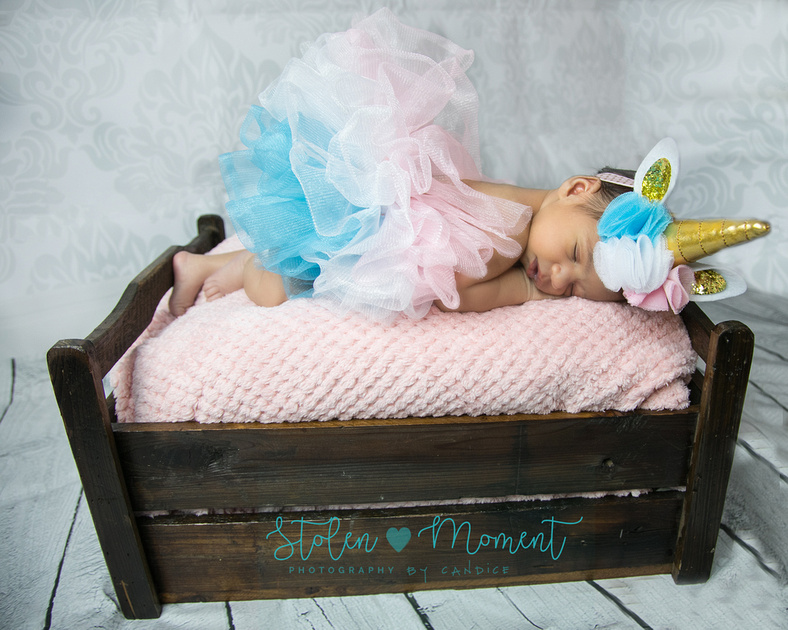 "a newborn girl lays on a wooden ""bed"" dressed in a unicorn tutu and hat"