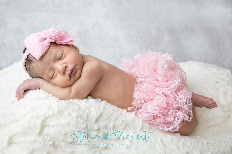a newborn girl lays on her tummy sleeping dressed in pink lace diaper cover and pink bow on her head