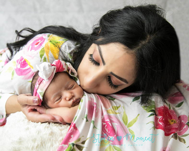 a mom in a floral robe lays her head on her newborn daughter's back (in matching robe) and gives her a kiss on the cheek