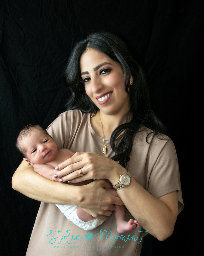 a beautiful mom holds her newborn daughter in her arms