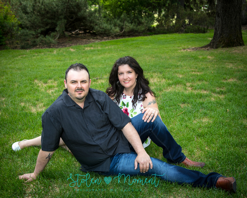 A man and his fiance sit on the grass at the Alberta Legislature Grounds
