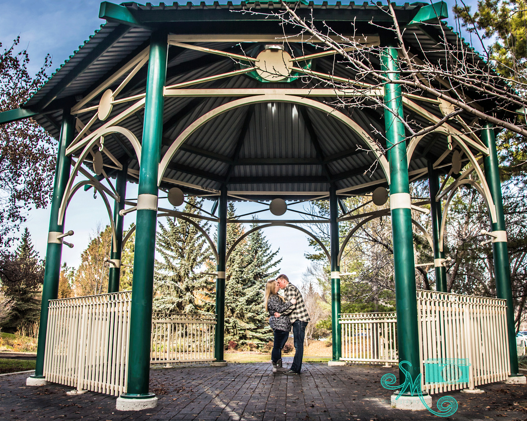 a man and a woman share a kiss in the gazebo