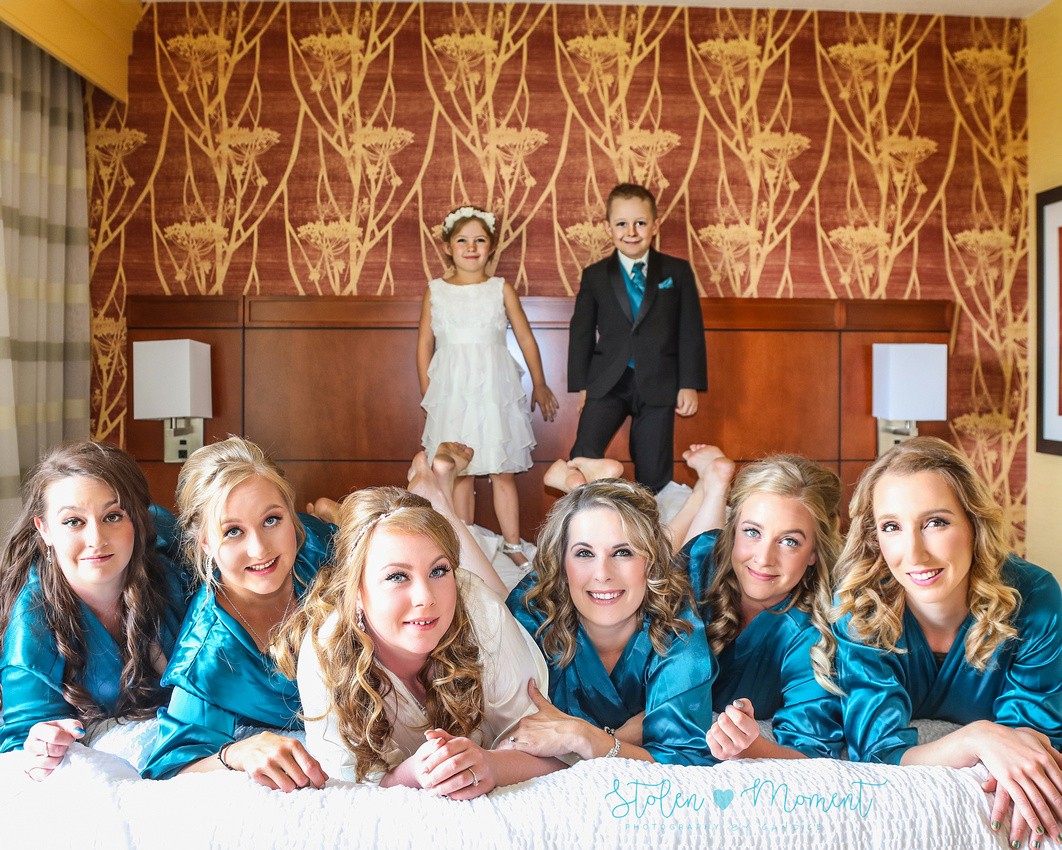 the bride and bridesmaids lay on the bed with the flower girl and ring bearer standing on bed behind them.