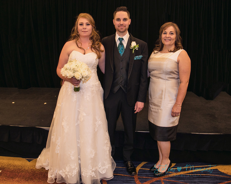 the bride and groom stand with the groom's mother