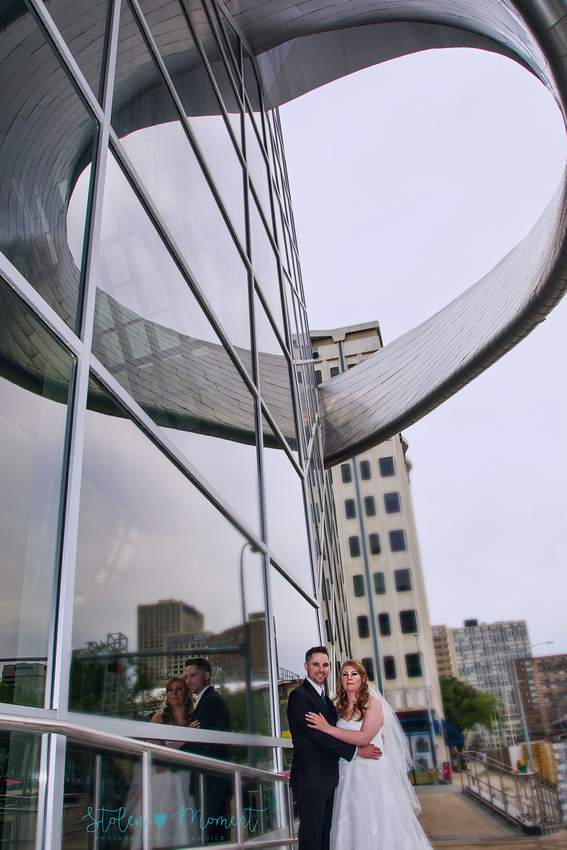 the bride and the groom outside the Art Gallery of Alberta stand underneath an overhang that makes the shape of a heart