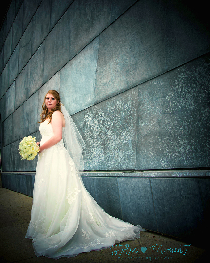 the bride stands in front of a wall outside the Art Gallery of Alberta