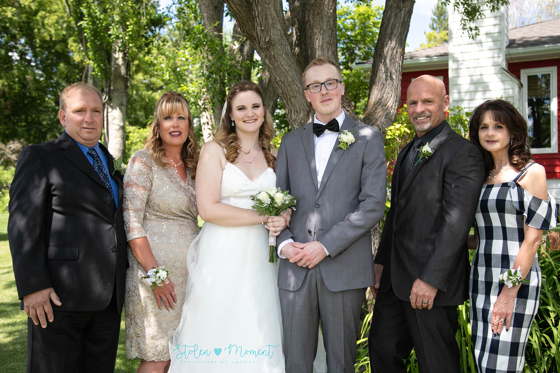 the bride and groom with the groom's mom, dad, step mom and step dad