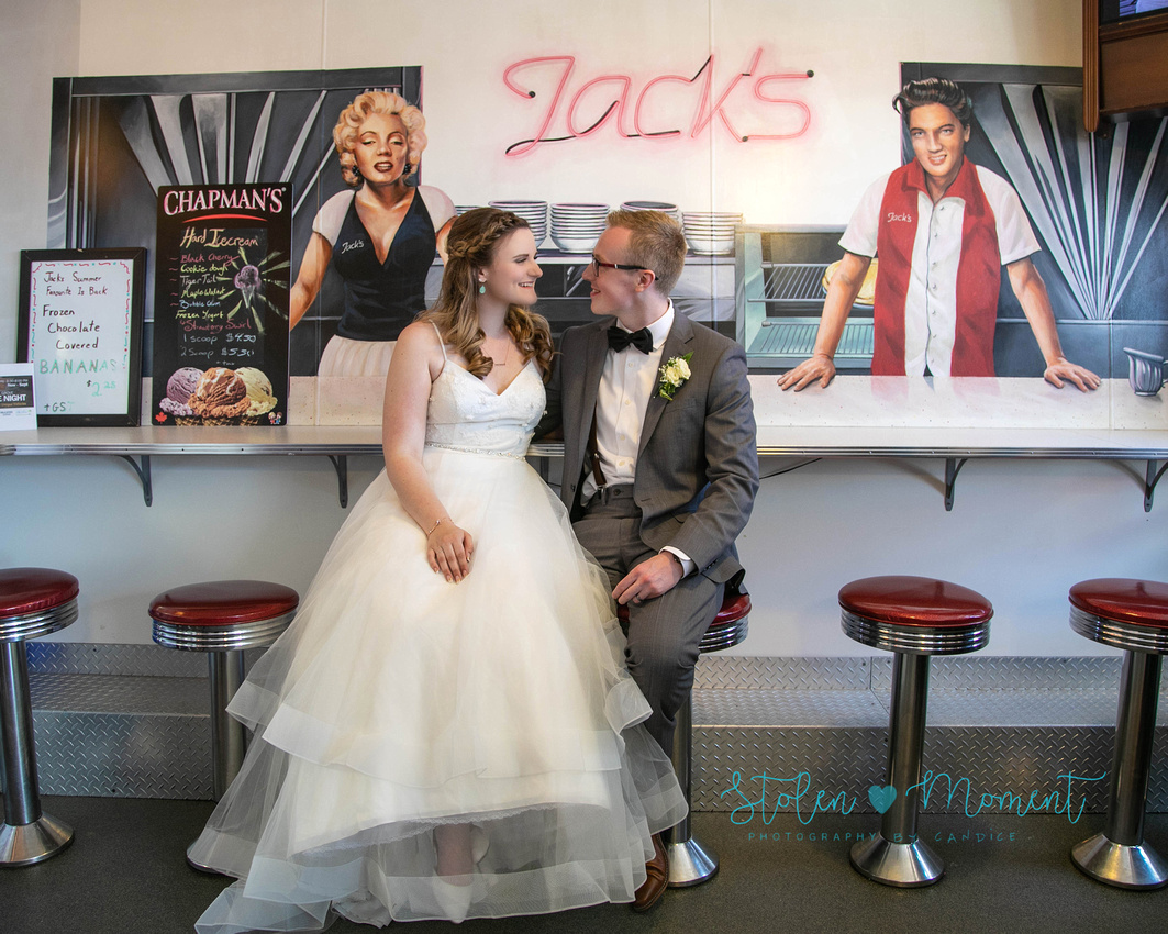 a bride and groom sit on round red stools at Jack's drive inn in Spruce Grove and look at each other smiling