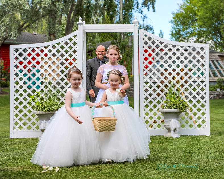 two flower girls and a junior bridesmaid walk down the aisle