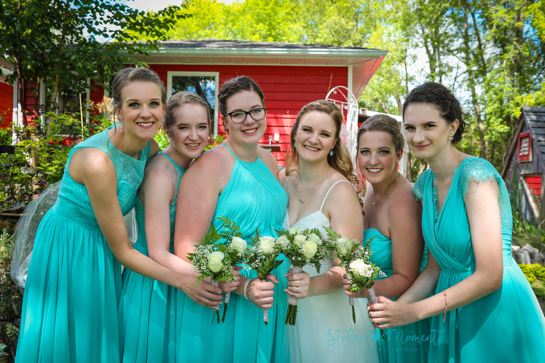 the bride stands between her bridesmaids