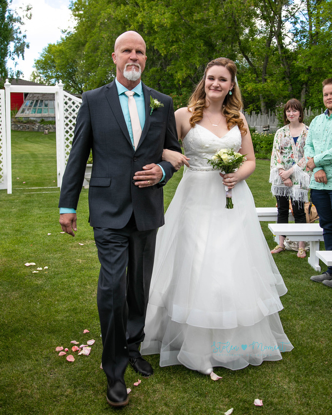 the bride and her father walk down the aisle