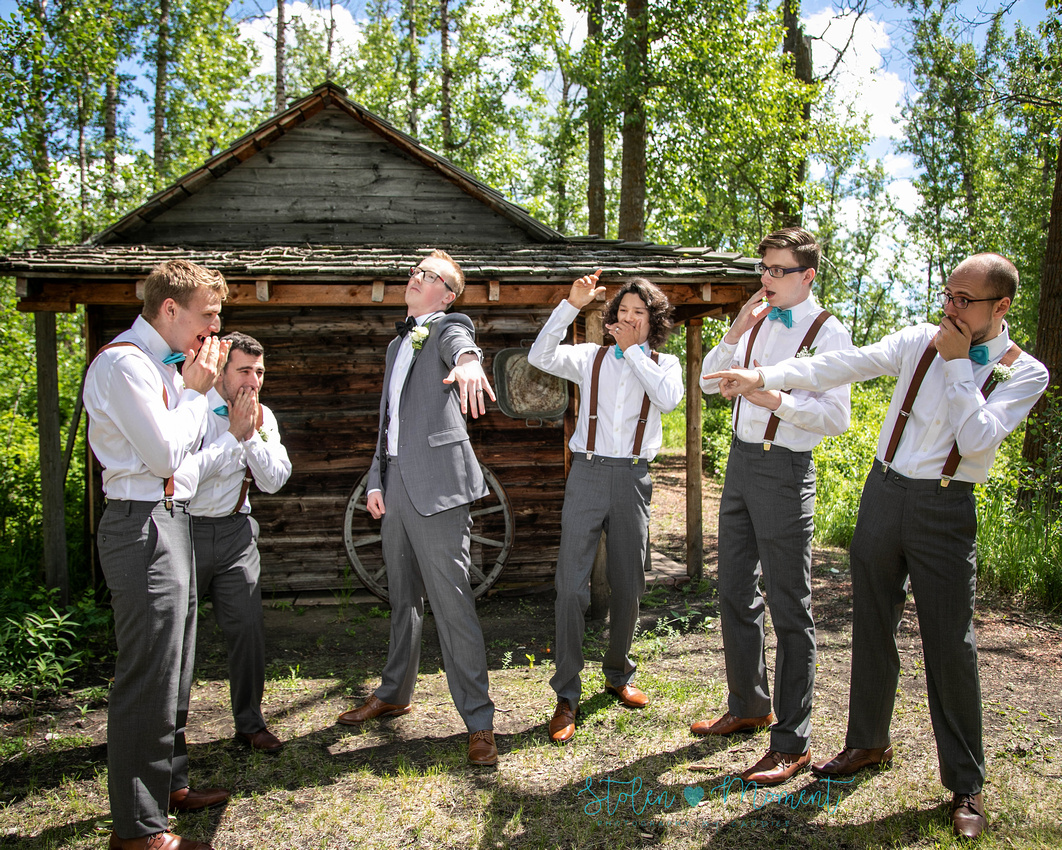 the groom shows off his ring in a fun shot with his groomsmen while the groomsmen react in awe