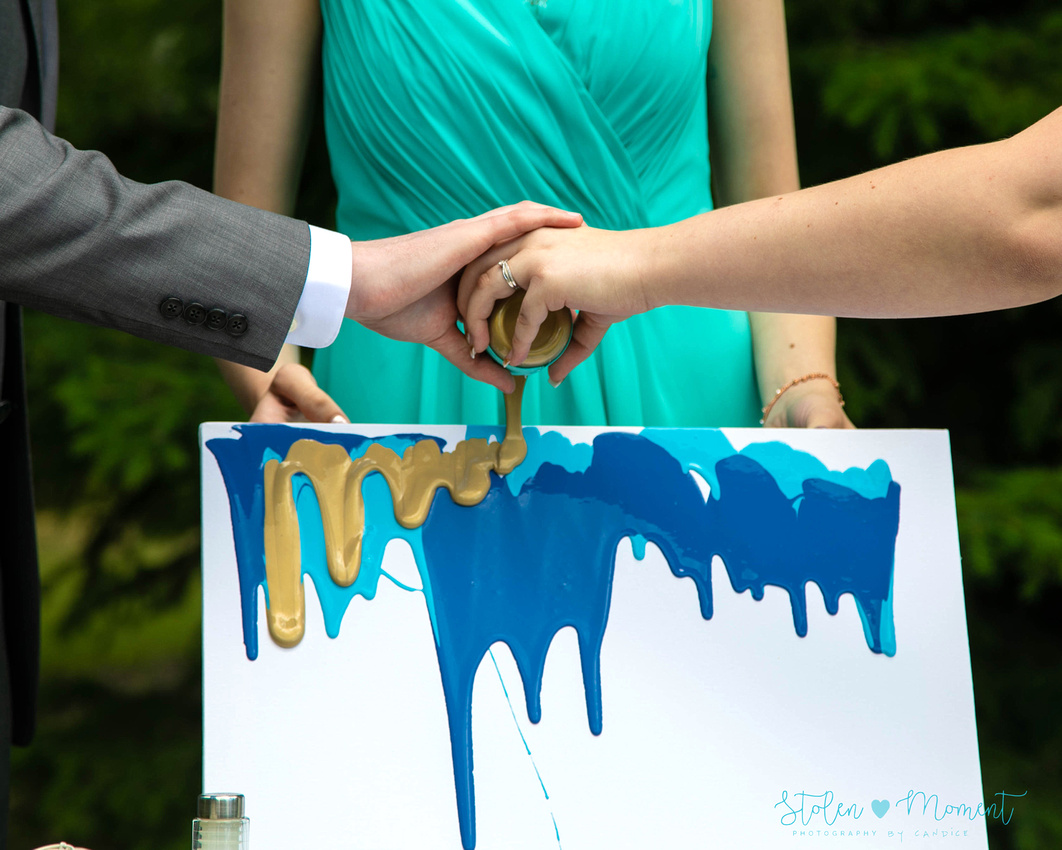 a bride and groom's hands as they pour the last of three colours of paint on a canvas - a substitute for a sand ceremony