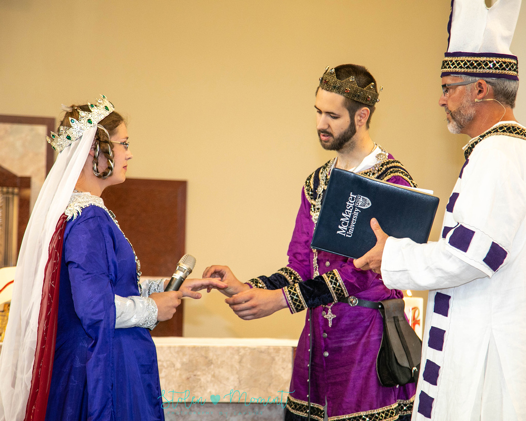 the groom dressed in fourteenth century costume, puts the ring on the bride's finger