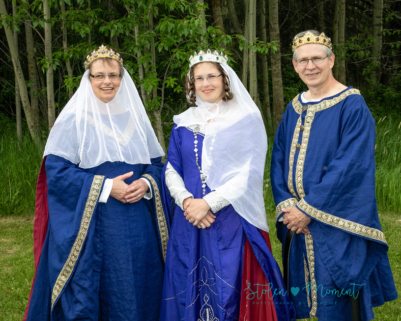 a bride stands with her mother and father - all of whom are dressed in traditional fourteenth century costumes
