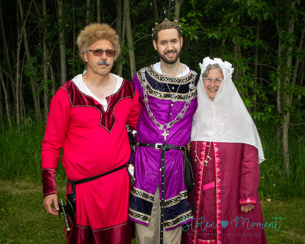 a groom stands with his mother and father, all of whom are dressed in fourteen century costume