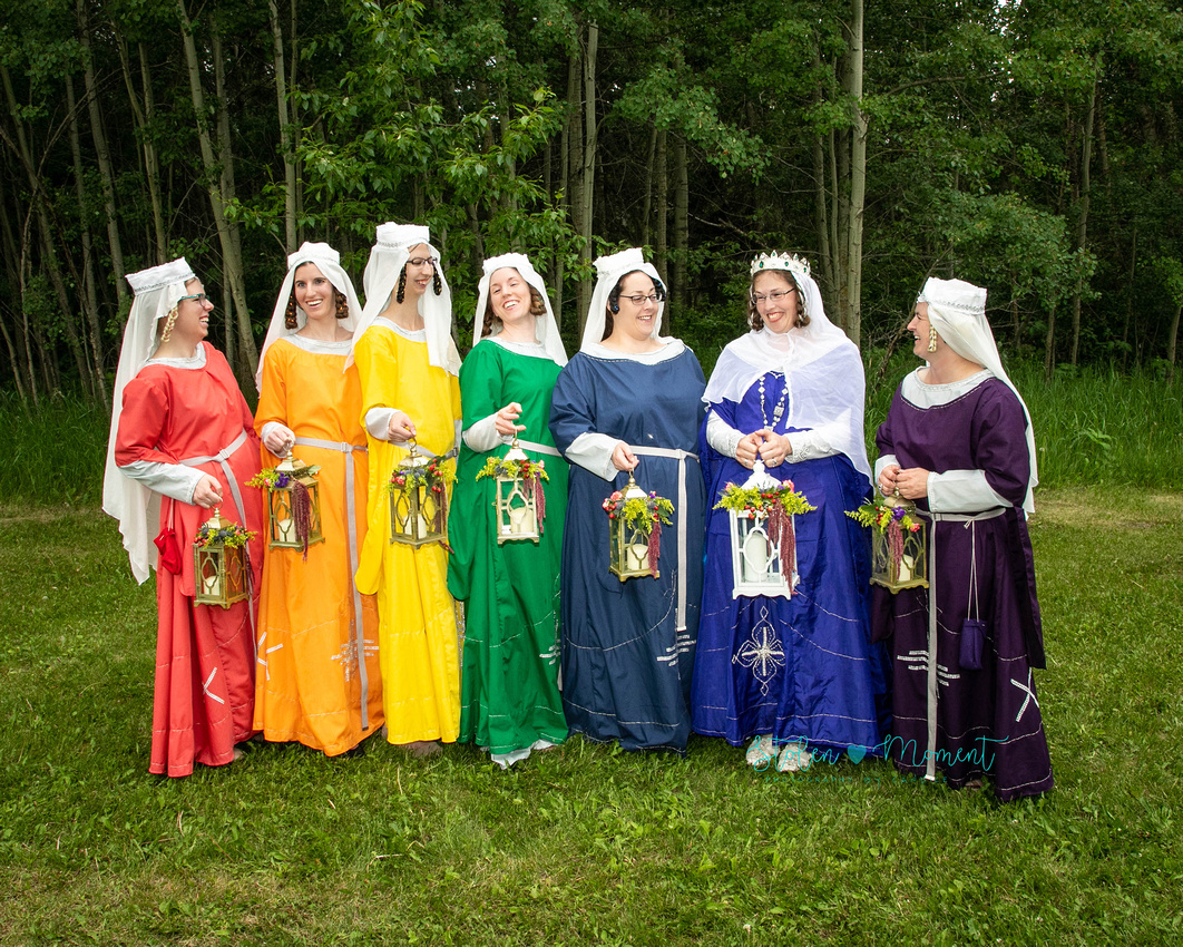 the bride and her maids stand in a line in traditional medieval costume holding lanterns and sharing a laugh between themselves