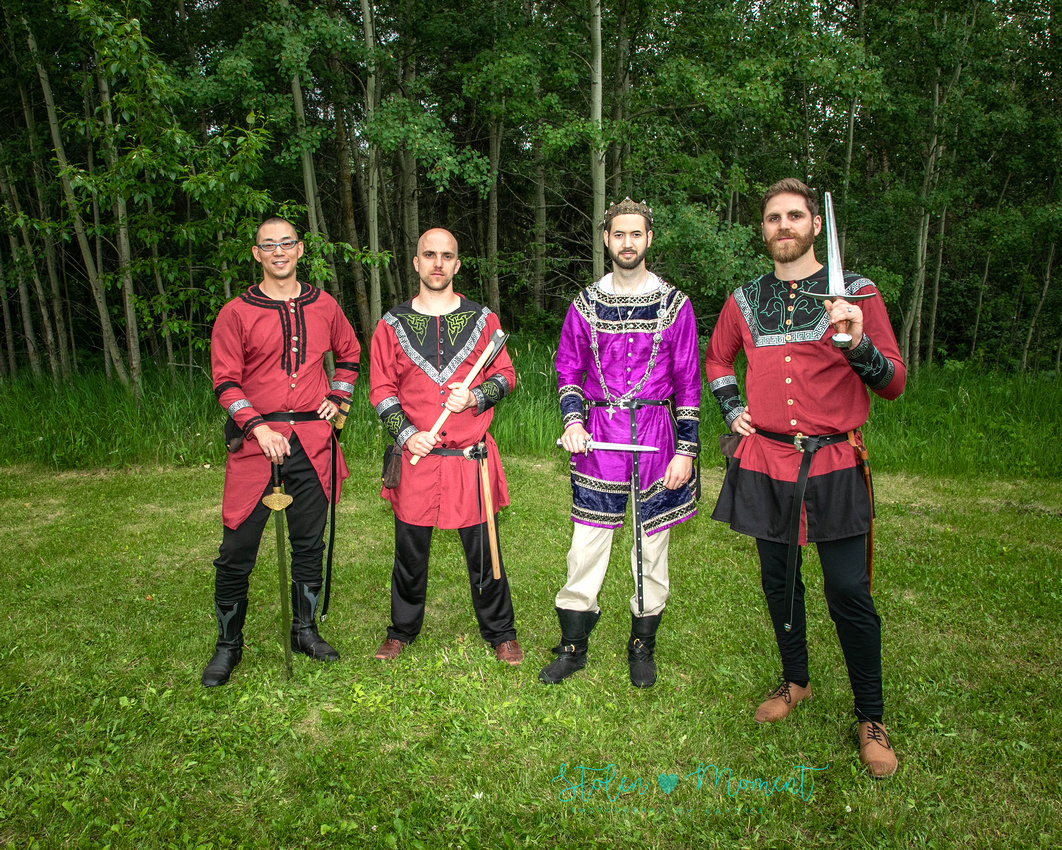 the groom stands between his three guards all holding various fourteenth century weapons and dressed in fourteen century garb.