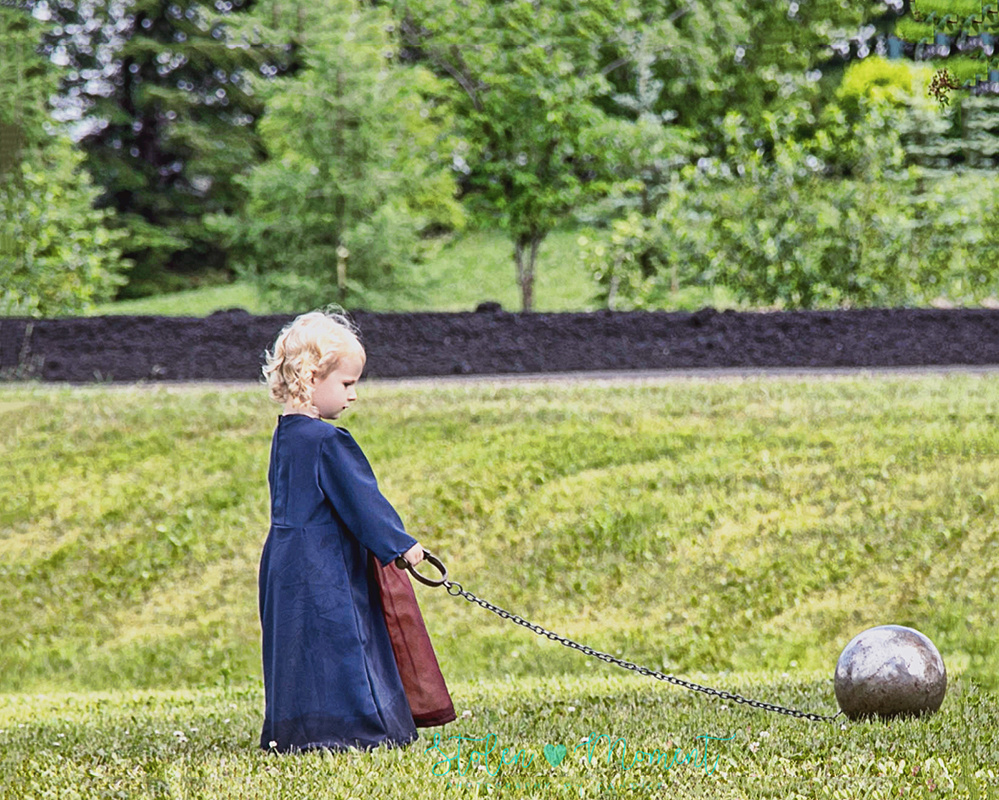 """a little girl dressed in medieval costume pulls along a """"ball and chain"""" during a medieval wedding reception outdoors"""