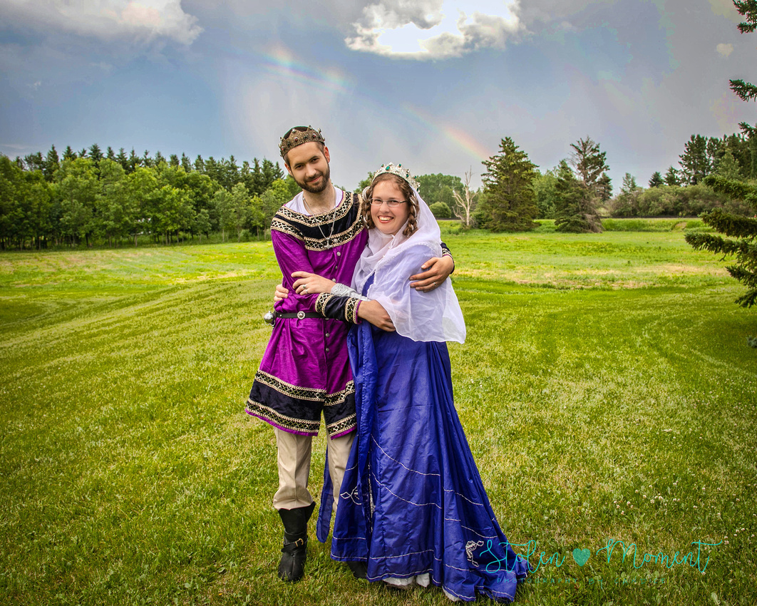 a bride and groom in each other's arms smiling at the camera both dressed in medieval costumes with a rainbow in the sky behind them