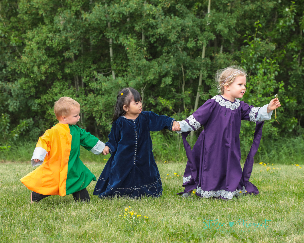 three children from a medieval wedding, all dressed in traditional costume hold hands and walk across the grass, with a girl in the lead carrying a dandelion