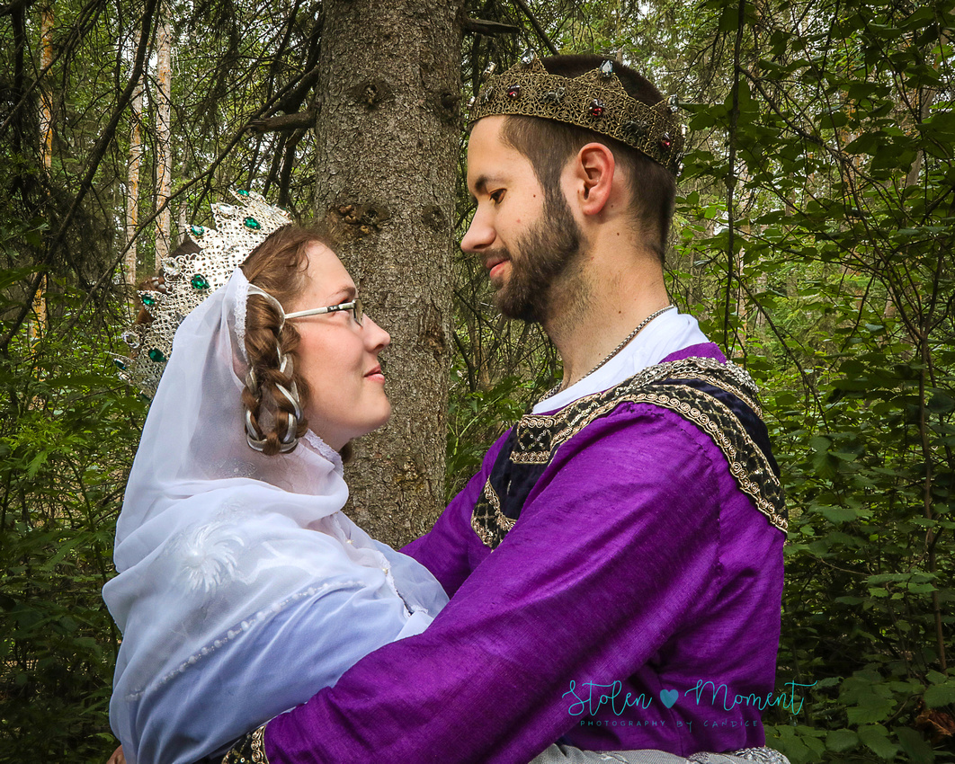 """the bride and groom dressed in medieval costumes look into each other's eyes while standing in a """"forest"""""""