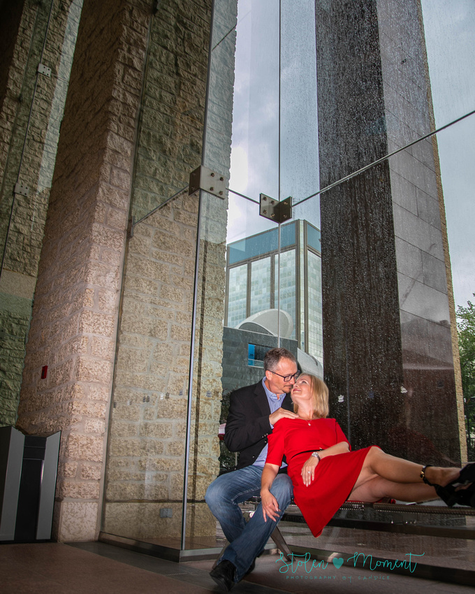 a man and his fiancé sit on a bench in front of the glass windows at city hall