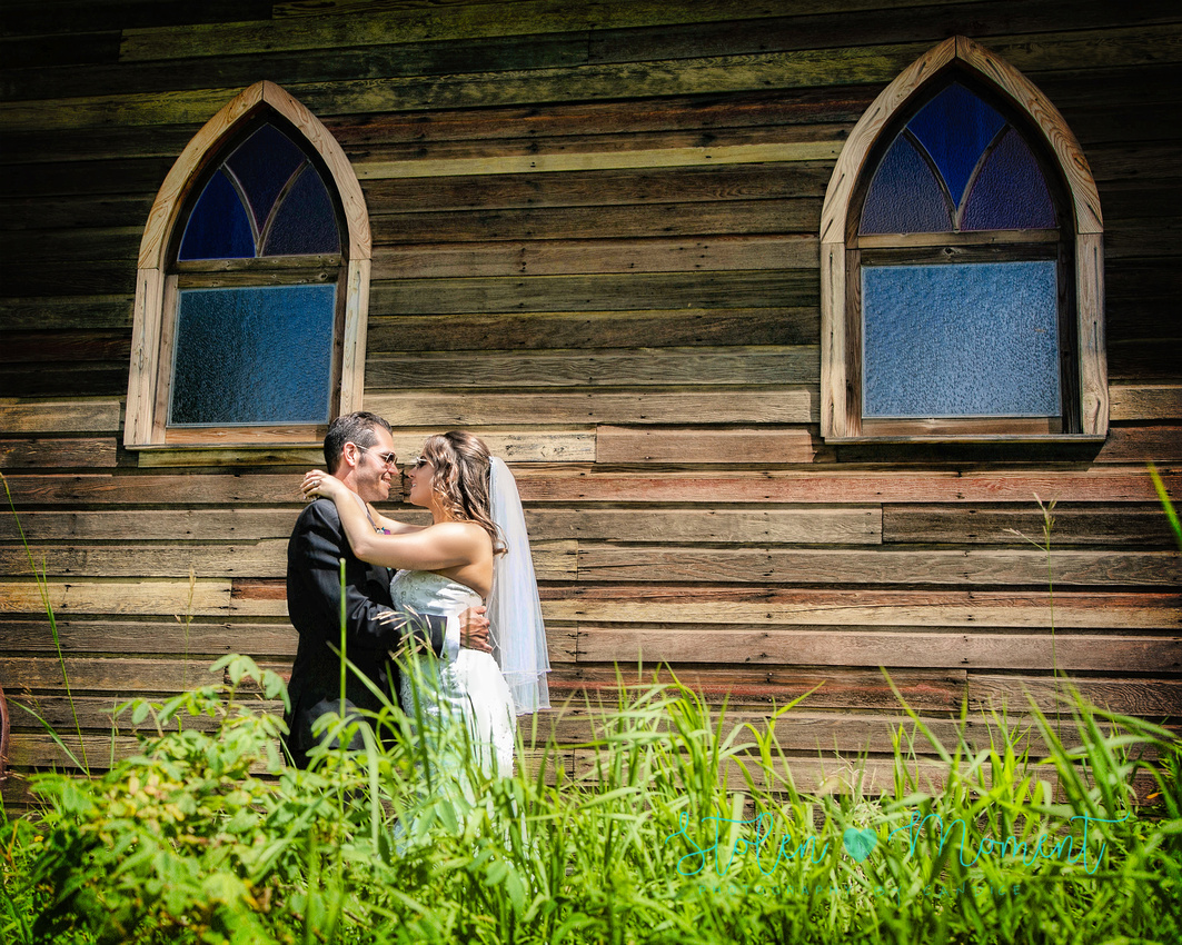 a bride and groom in each others arms looking into each others eyes in front of an old wooden church at Hastings lake Gardens