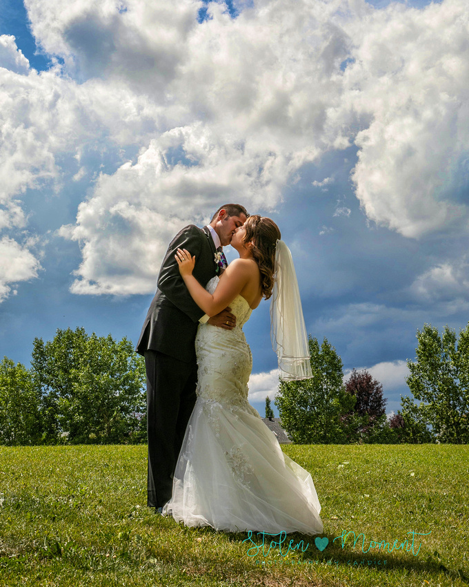 a bride and groom share a kiss on a hill top in Sherwood Park with fluffy white clouds and blue sky overhead