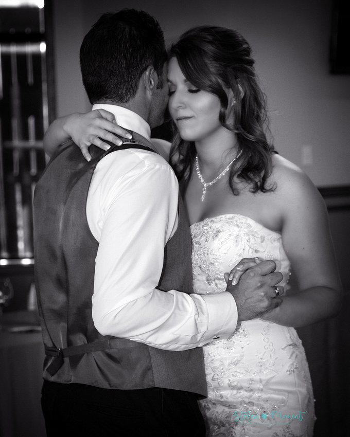 the bride and groom share their first dance and the bride has her eye closed enjoying the moment