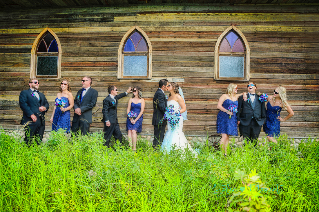 a wedding party of ten stand in front of an old wooden church at Hastings Lake Gardens.  The party share a laugh while the bride and groom kiss