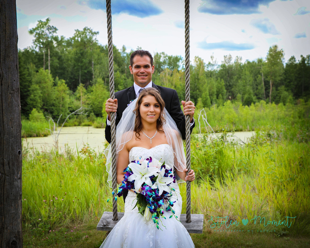 a groom stands behind a swing as his bride sits on the swing at Hastings Lake Gardens