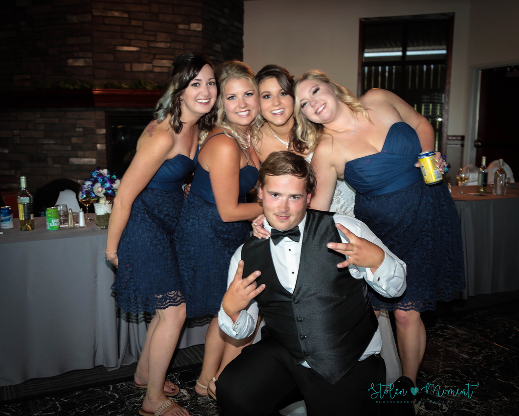 the bride with three of her bridesmaids and one groomsmen strike a fun shot during the reception