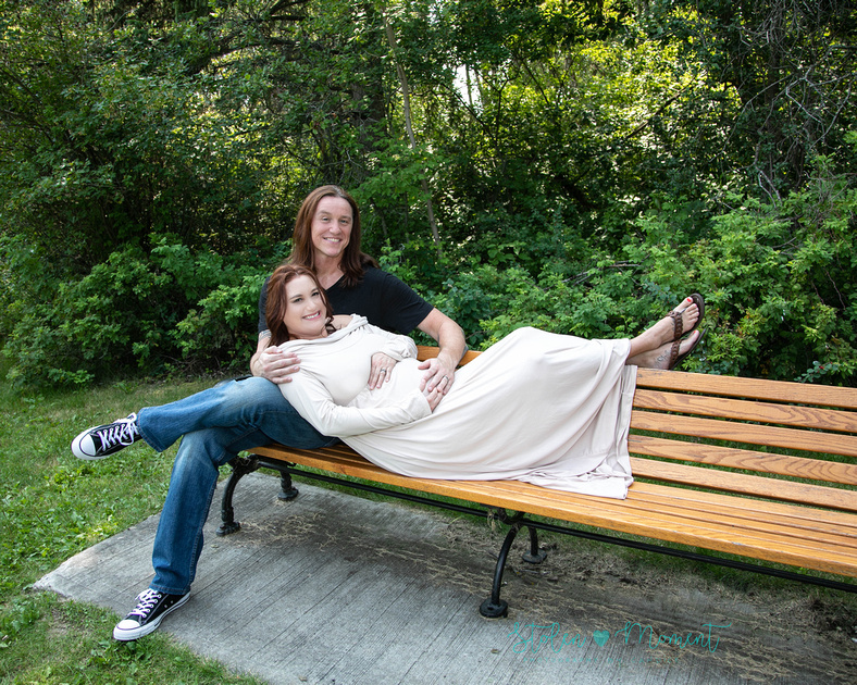 a man sits on a bench while his pregnant wife lays her back into his lap and places her feet up on the bench at William Hawrelak Park