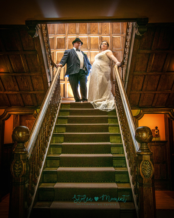 the groom strikes a gangster-like pose at the top of the stairs at Rutherford House while the bride stands beside him striking a pose fit for a gangster's wife