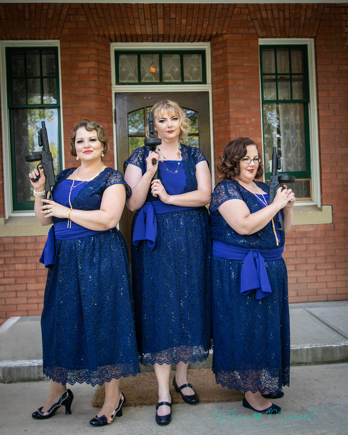 the three bridesmaids stand on the steps of Rutherford House and strike the classic Charlie's Angels pose while holding Tommy guns